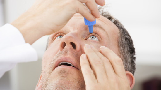 Mature Man Putting Eye Drops In Eyes